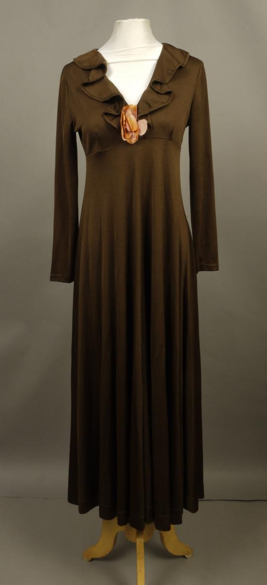 88dd433ea0b8 An early 1970s Frank Usher full length evening gown in brown crimplene  having V neckline with wavy collar and flower detail, full sleeves and a  full skirt