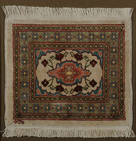 A CAUCASIAN MINIATURE SILK RUG, with a central floral medallion with corner spandrels on a cream field